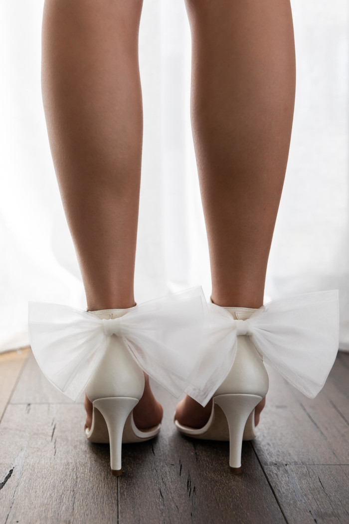 A model wearing the Grace Loves Lace Immi Bows with the white Dosa Heels