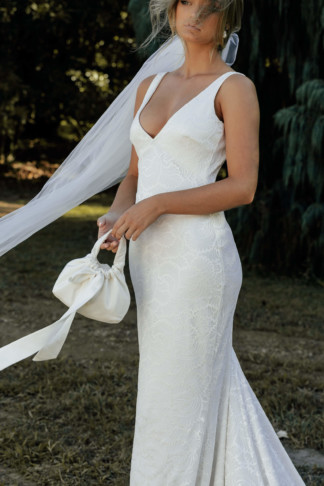Bride standing in front of a tree wearing the River gown, the Posey Short Veil & holding the Martini bag handmade of crepe