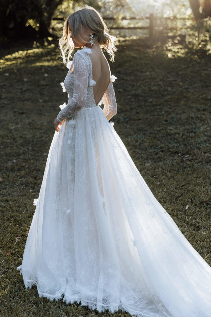 Bride standing in a grassy field where the sun is setting, wearing the long sleeve Monet wedding gown