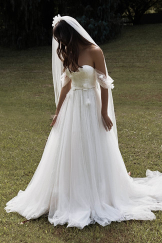 A bride standing on grass wearing a beautiful tulle wedding dress called The Star, also wearing the Monet veil