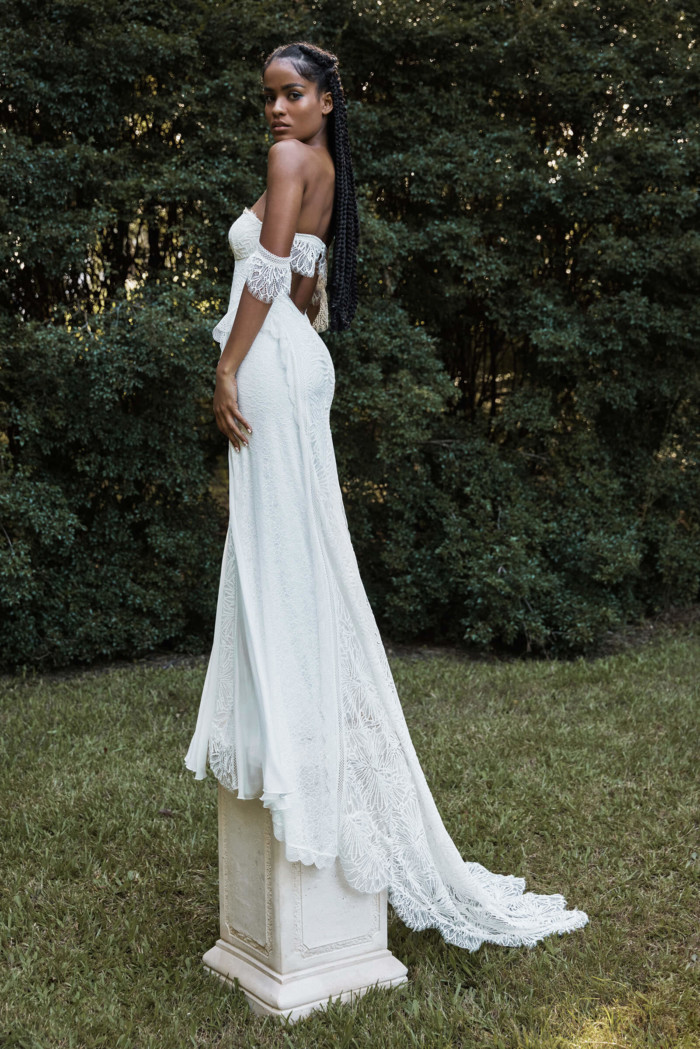 Bride standing on a pillar behind a large hedge, wearing the Noah gown with braids in her hair