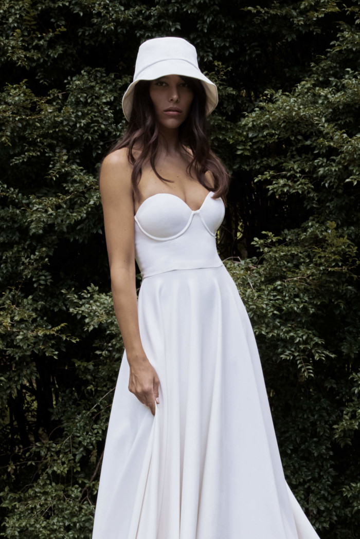 A bride wearing an ivory bucket bag by Grace Loves Lace called the Lou Hat