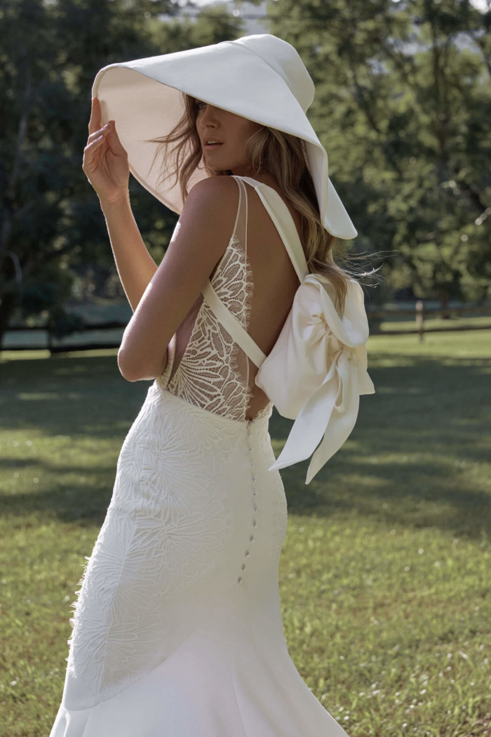 Bride standing in a grassy field wearing the Lena Gown, Grace backpage & the Helena hat from the Elysian Collection