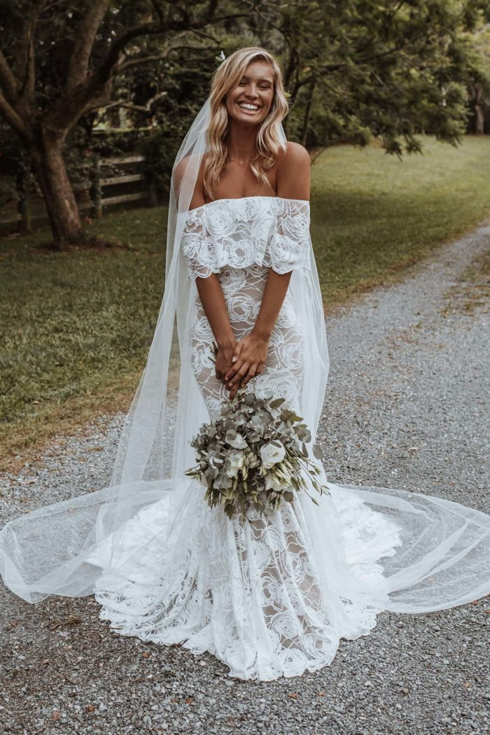 Blonde bride to be wearing off-the-shoulder Peaches wedding dress with nude-tone lining paired with the Henri veil made of Tulle