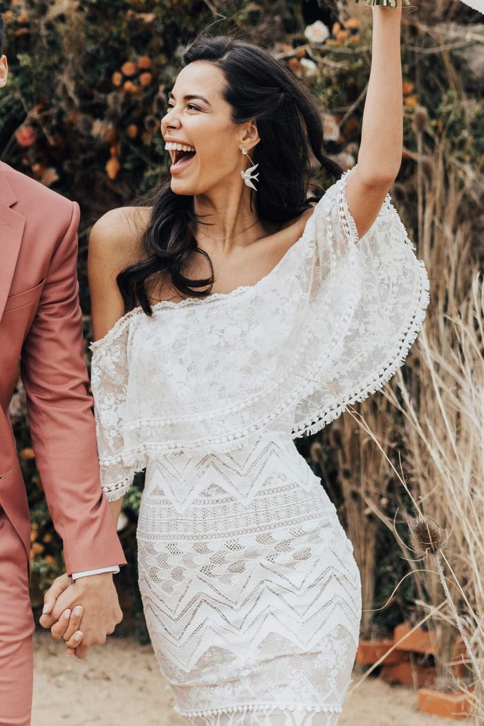 Brunette bride wearing Grace Loves Lace Emanuela Gown holding hands with groom
