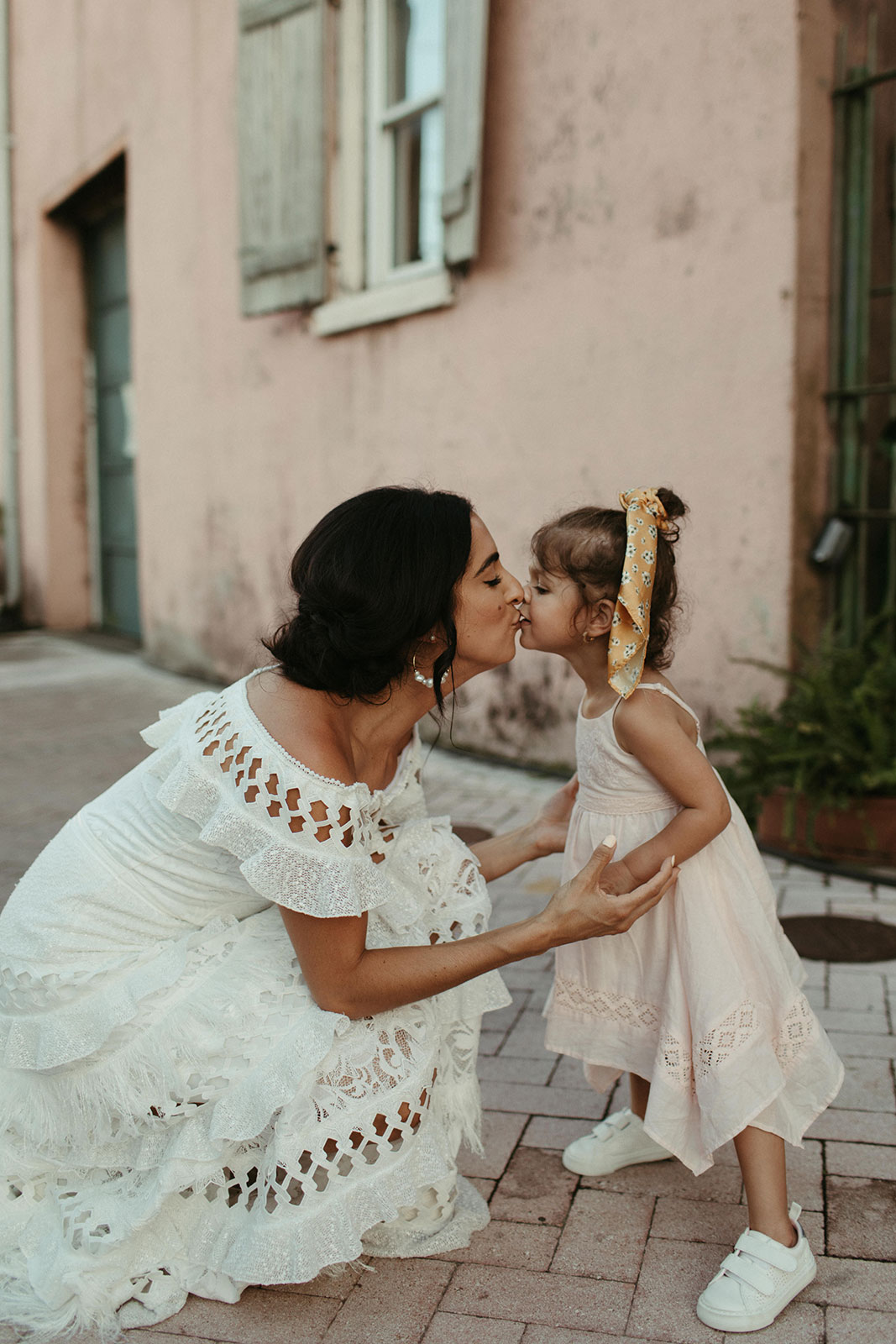 bride wearing Grace Loves Lace Coco Gown crouching down kissing young girl