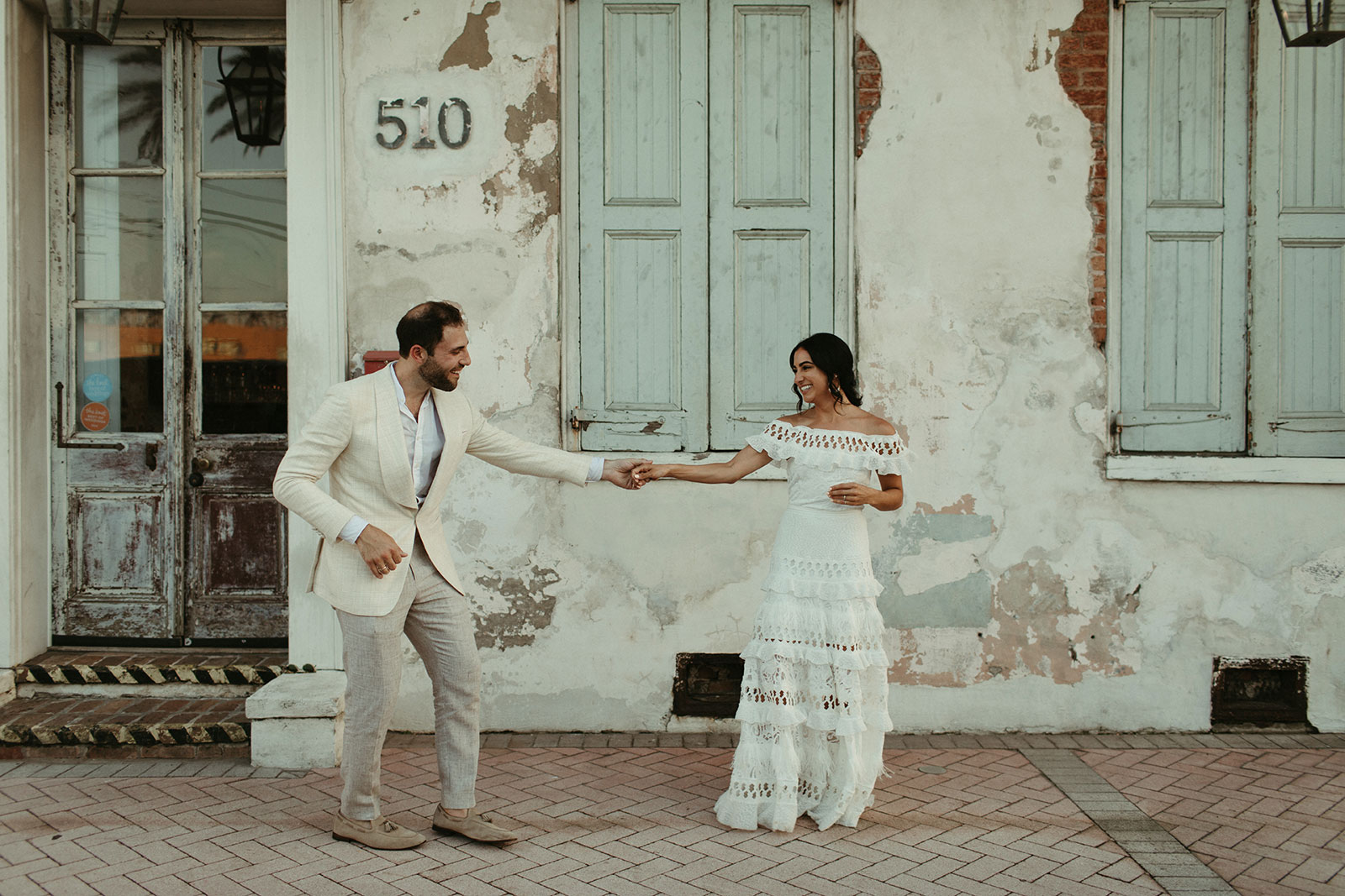 Brunette bride wearing Grace Loves Lace Coco Gown dancing with groom