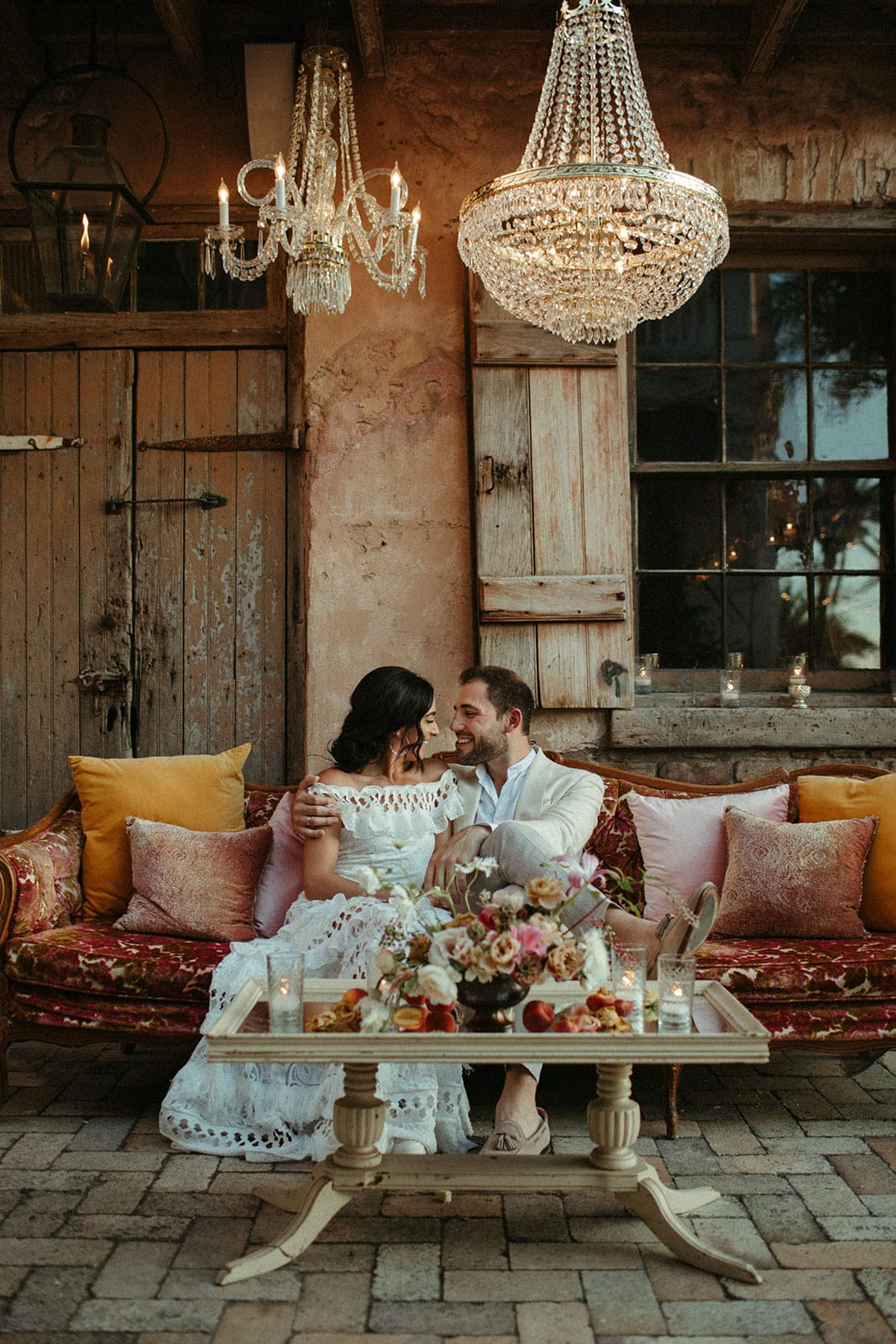 Brunette bride wearing Grace Loves Lace Coco Gown being held by groom sitting down on red sofa