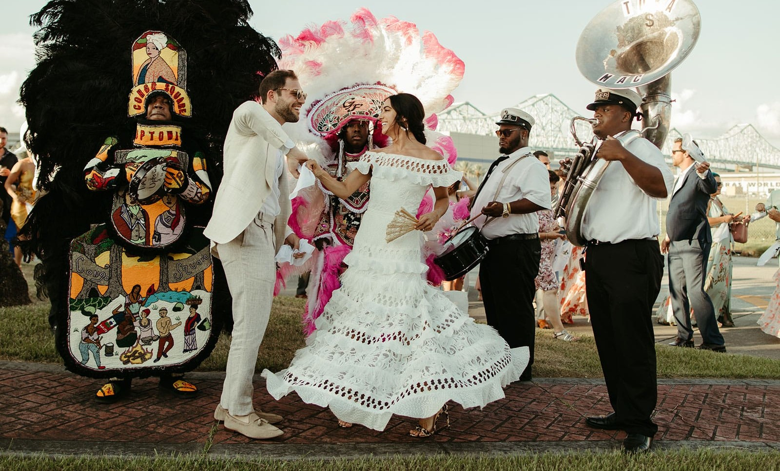 Brunette bride wearing Grace Loves Lace Coco Gown dancing with groom in parade