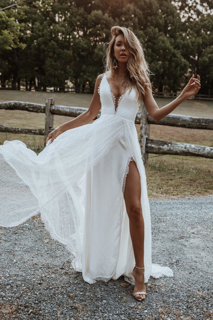 Bride wearing Grace Loves Lace Song Gown holding skirt in hand