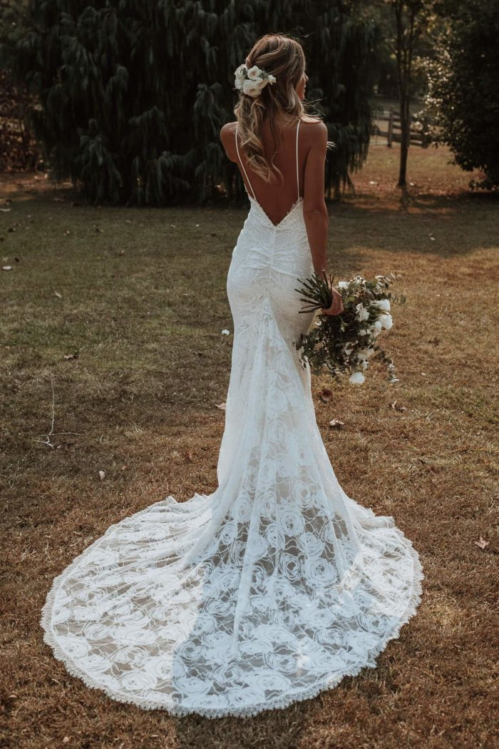 Back shot of bride wearing Grace Loves Lace Clo Gown with bouquet in hand and flowers in hair