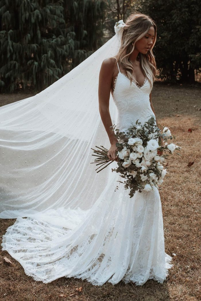 Bride wearing Grace Loves Lace Clo Gown with bouquet in hand and flowers in hair