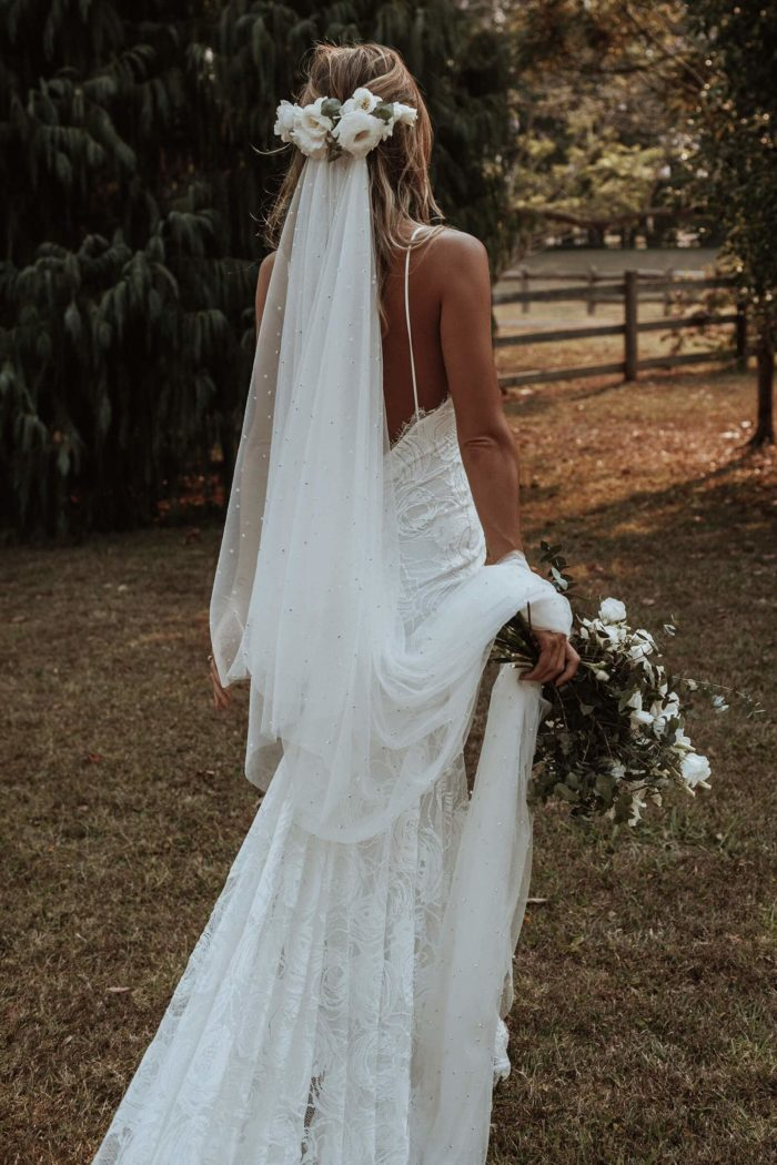 Back shot of bride wearing Grace Loves Lace Clo Gown with flowers in hair and bouquet in hand