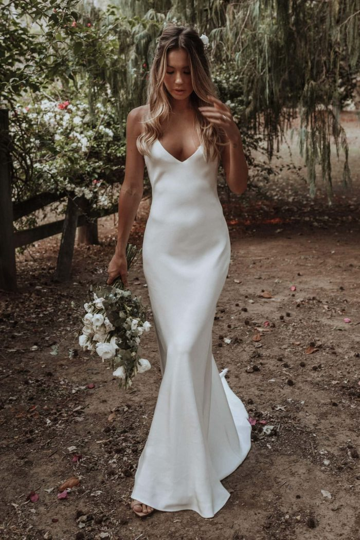 Blonde bride wearing Grace Loves Lace Dove Gown holding bouquet in garden