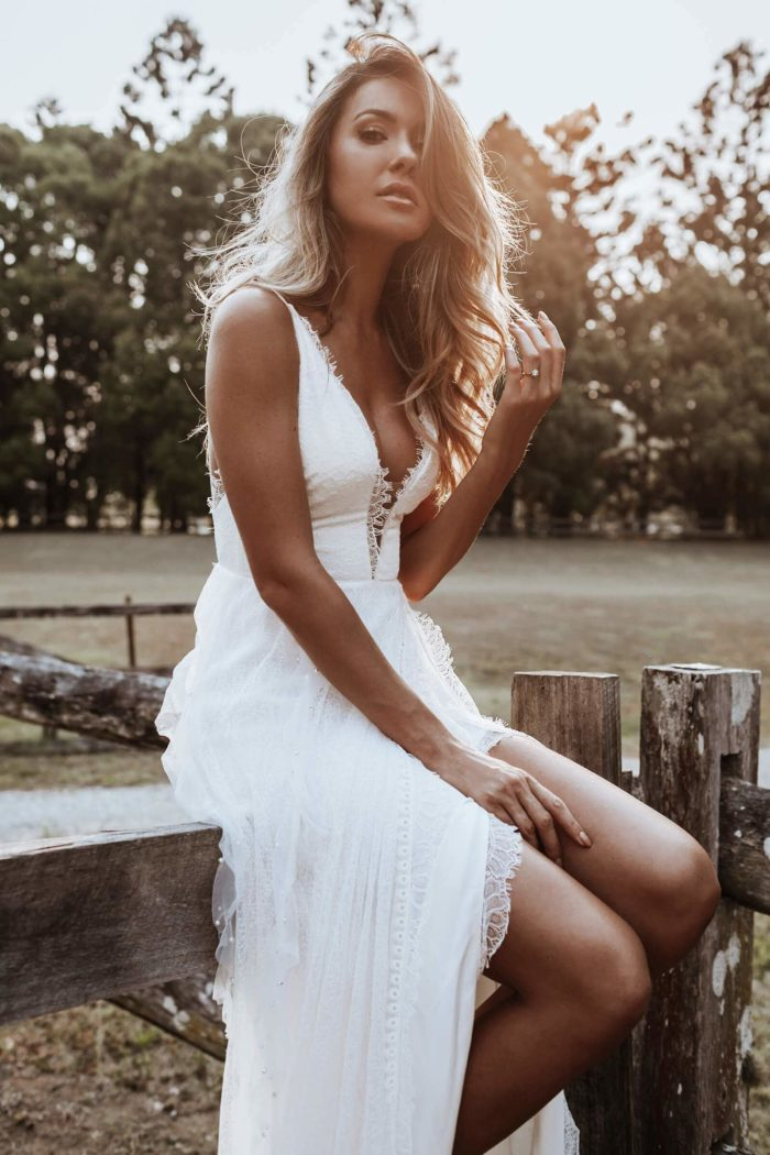 Bride wearing Grace Loves Lace Song Gown sitting on wooden fence