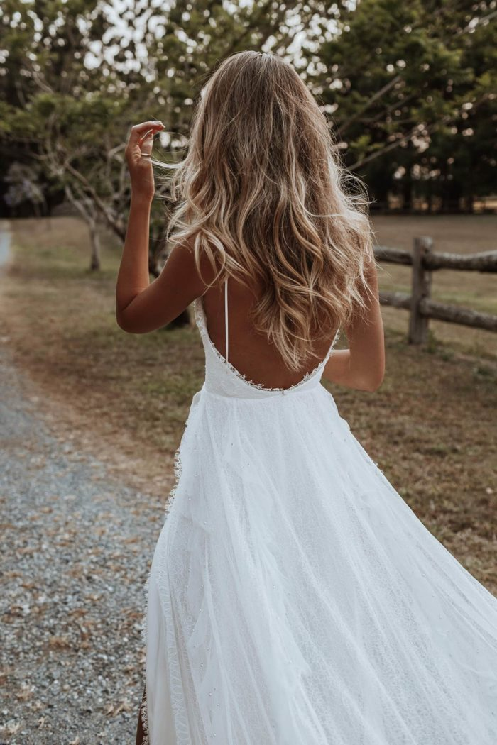 Back shot of bride wearing Grace Loves Lace Song Gown with hand in front of face
