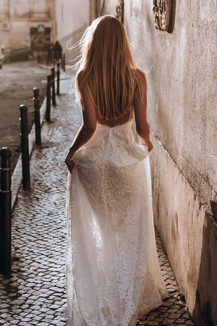 Back shot of bride wearing Grace Loves Lace Darling Gown holding skirt in hands