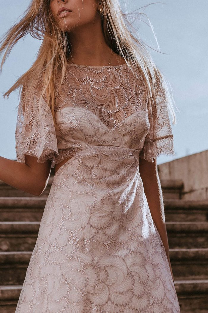 Blonde bride wearing Grace Loves Lace Capri Gown in front of stairs