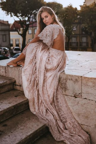 Blonde bride wearing Grace Loves Lace Capri Gown sitting on stone wall