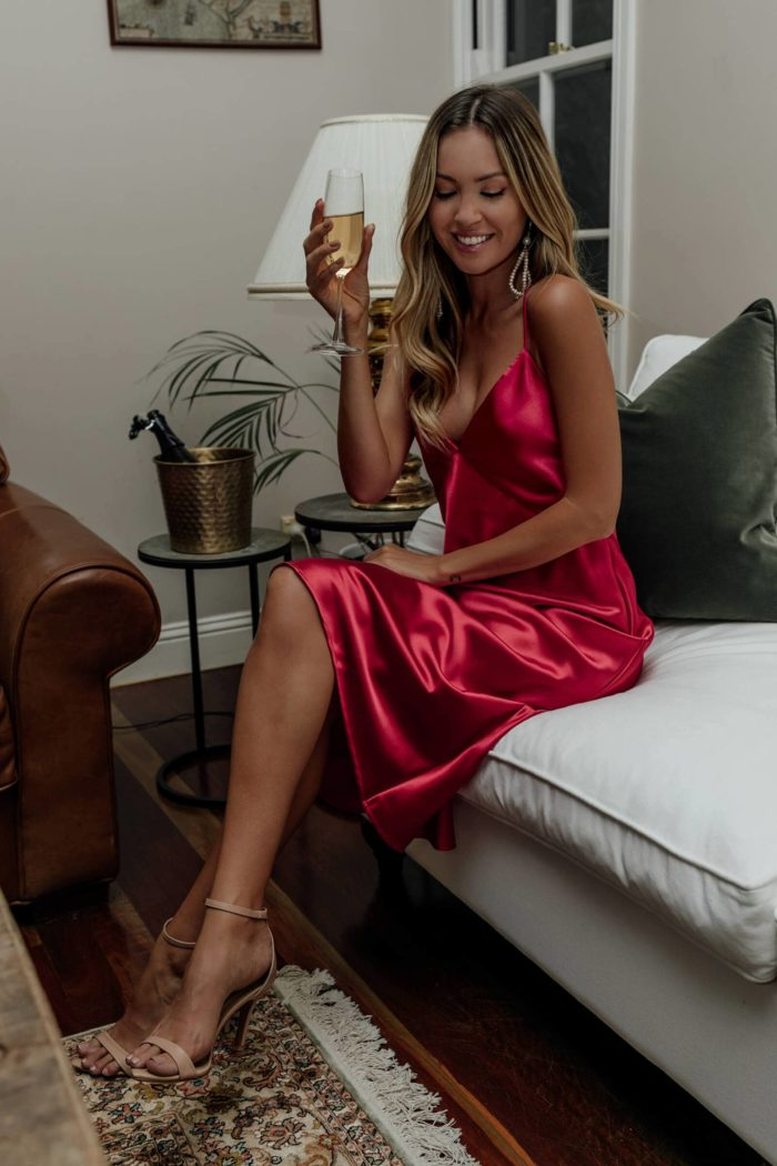 Blonde bridesmaid wearing Grace Loves Lace Silky Satin Midi in Ruby sitting on sofa holding champagne glass