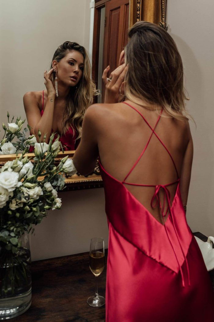 Brunette bridesmaid wearing Grace Loves Lace Silky Satin Midi in Ruby putting earring on looking in mirror