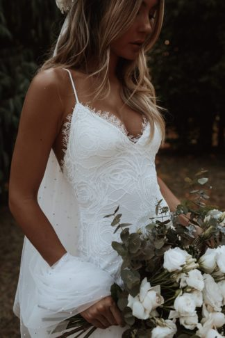 Bride wearing Grace Loves Lace Clo Gown holding bouquet