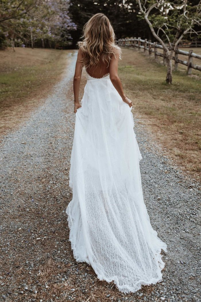 Back shot of bride wearing Grace Loves Lace Song Gown holding skirt in both hands