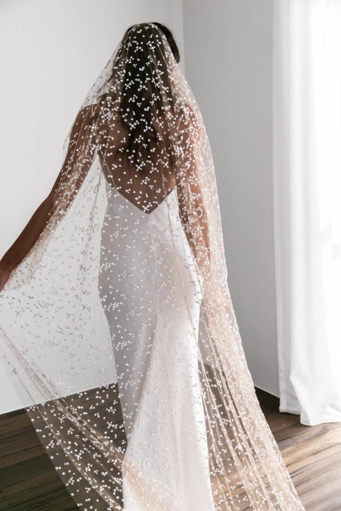 Back shot of brunette bride wearing Grace Loves Lace Menha Veil holding it in one hand