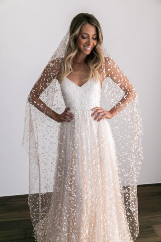 Blonde bride wearing Grace Loves Lace Menha Veil with hands on hips and the veil draped over her shoulders