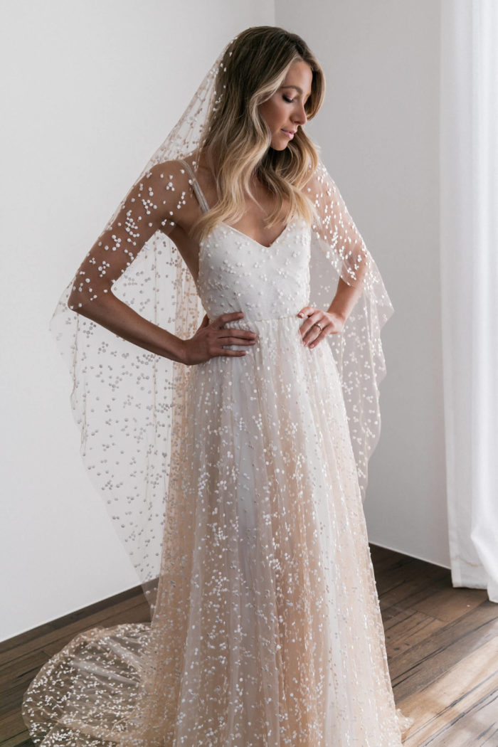 Blonde bride wearing Grace Loves Lace Menha Veil with hands on hips and veil draped over her shoulders
