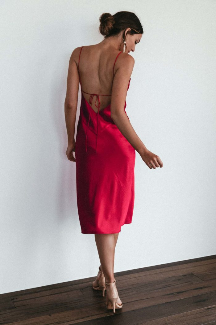 Back shot of bridesmaid wearing Grace Loves Lace Silky Satin Midi in Ruby and statement earrings