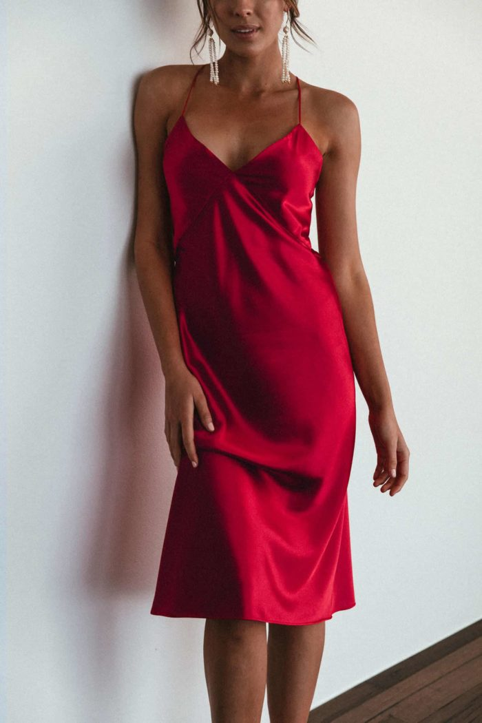 Bridesmaid wearing Grace Loves Lace Silky Satin Midi in Ruby leaning against wall