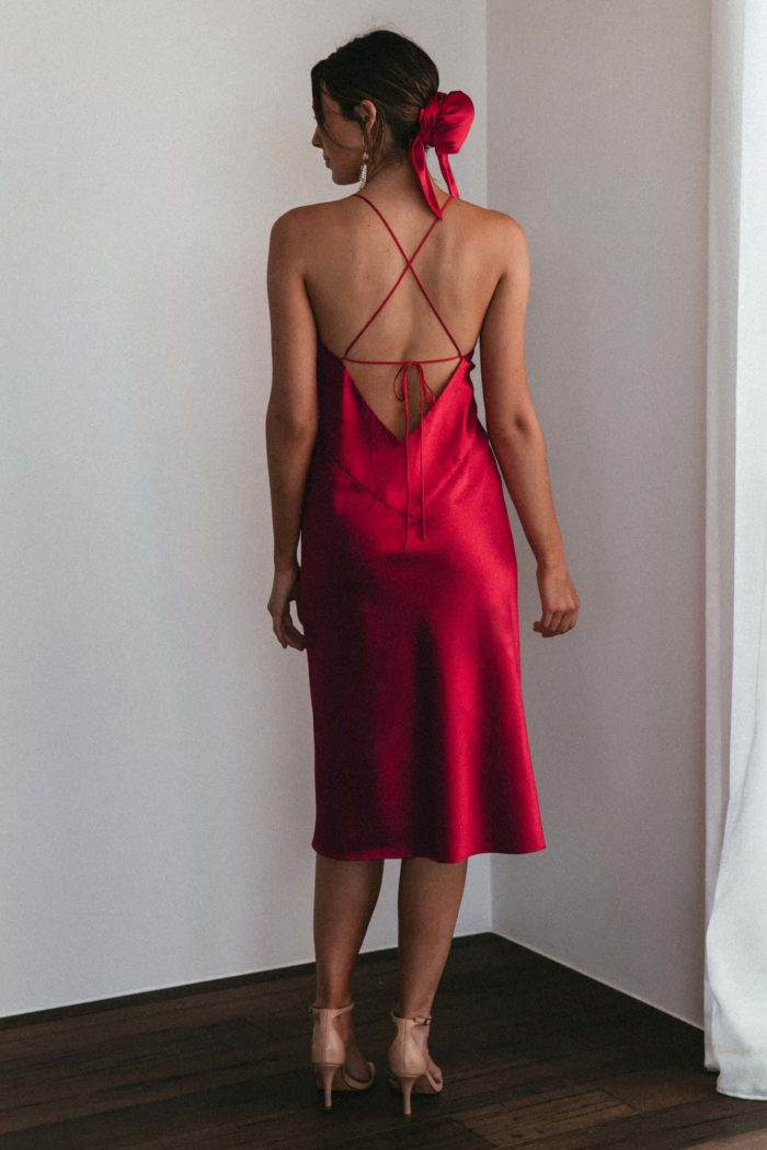 Back shot of brunette bridesmaid wearing Grace Loves Lace Silky Satin Midi in Ruby and hair bun