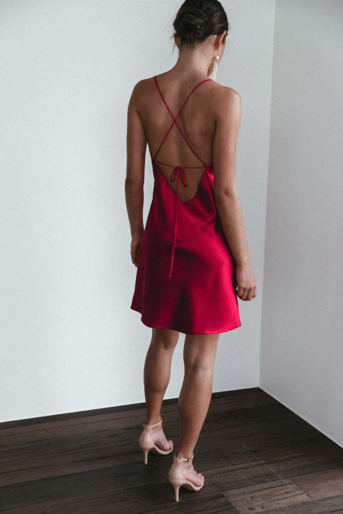 Back shot of bridesmaid wearing Grace Loves Lace Silky Satin Mini in Ruby and pearl earrings