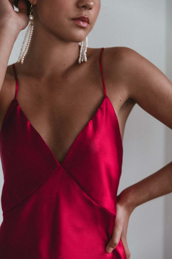 Bridesmaid wearing Grace Loves Lace Silky Satin Mini in Ruby with pearl earrings
