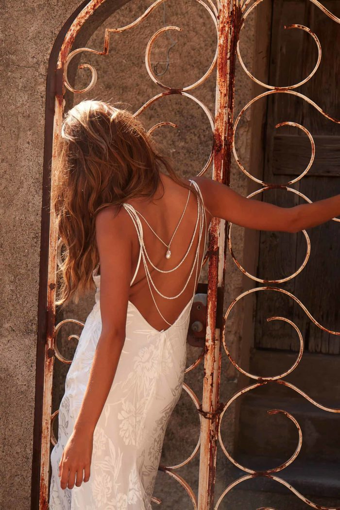 Back shot of bride wearing Grace Loves Lace Lucine Backpiece leaning against rusted gate