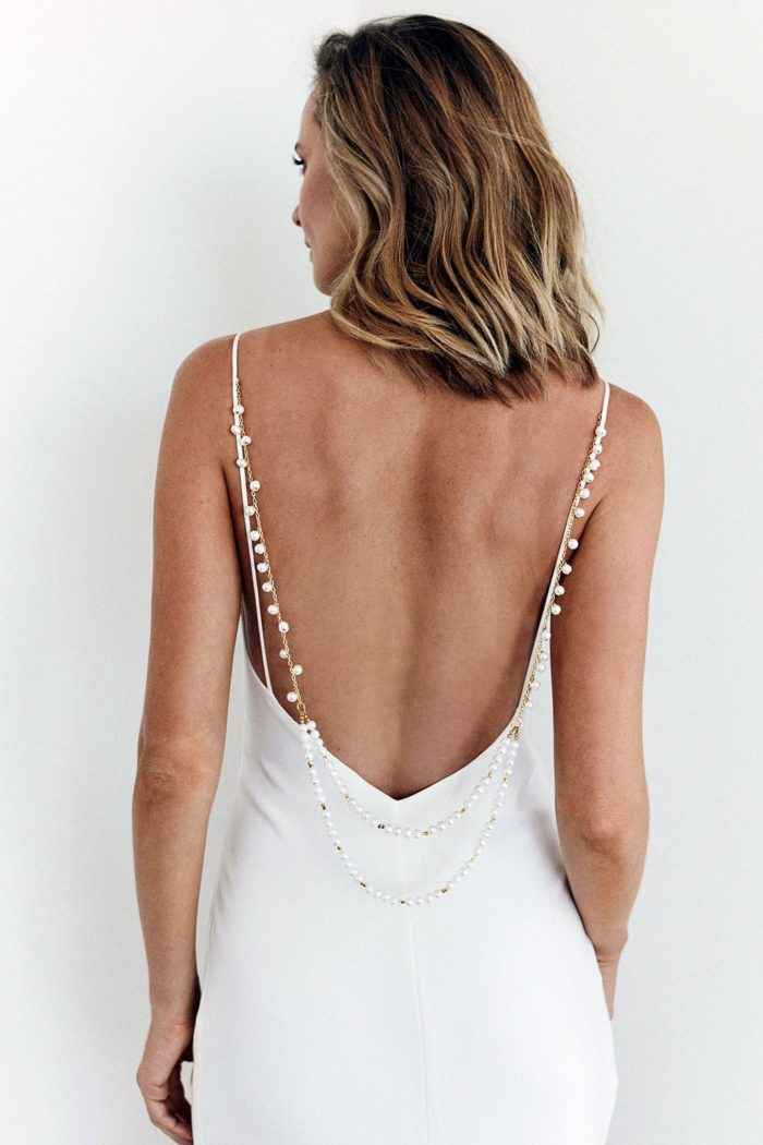 Back shot of bride wearing Grace Loves Lace Indira Backpiece looking to the side