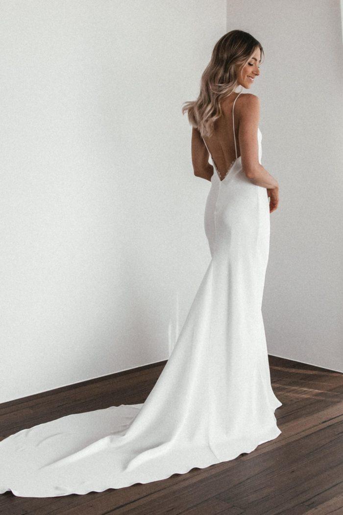 Back shot of bride wearing Grace Loves Lace Summer Eyelash Gown looking over shoulder