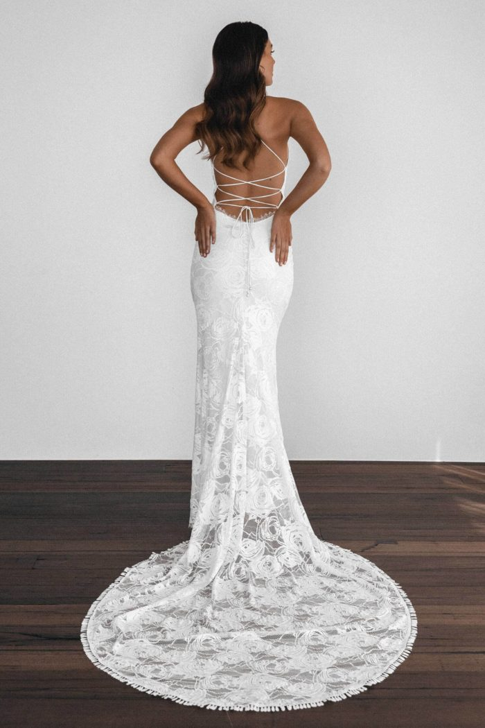 Back shot of brunette bride wearing Grace Loves Lace Honey Rose Eyelash Gown with hands on hips