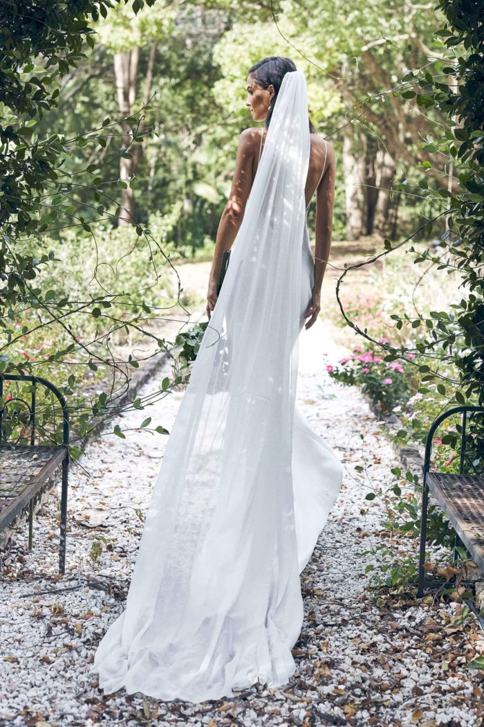 Back shot of Grace bride wearing Grace Loves Lace Gabriela Veil while walking down a pebbled pathway surrounded by greenery.