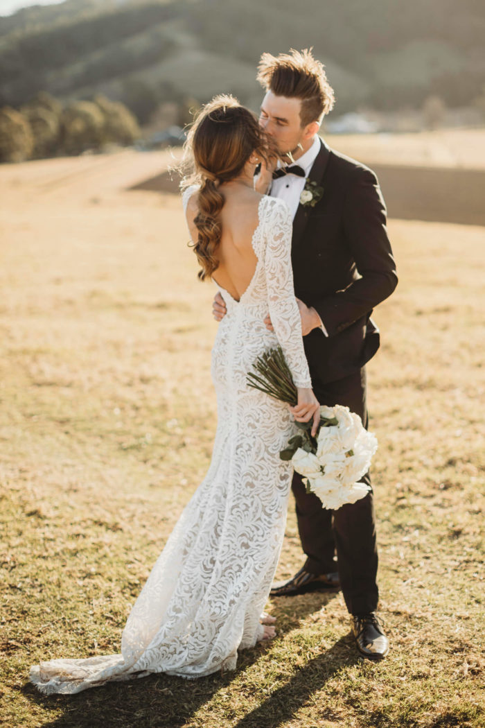 Bride wearing Grace Loves Lace Orla Gown holding bouquet kissing groom