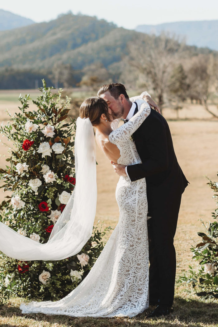 Bride wearing Grace Loves Lace Orla Gown kissing groom