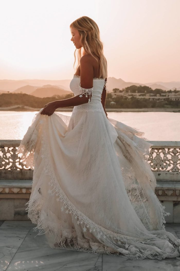 Blonde bride wearing Grace Loves Lace Fabienne 2.0 Gown holding skirt in hands