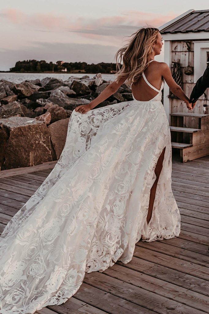 Blonde bride wearing Grace Loves Lace Megan Gown on wooden walkway beside the ocean