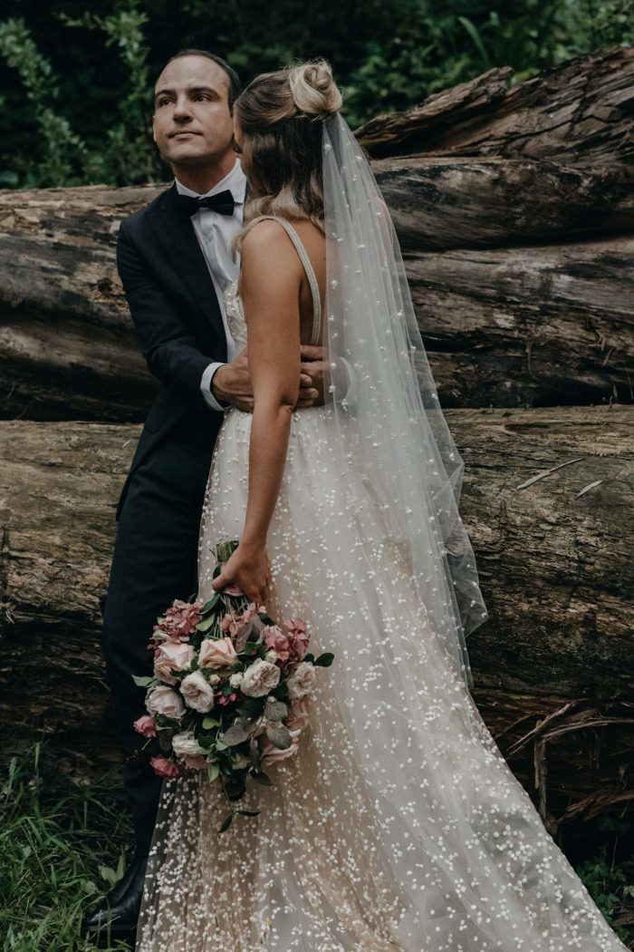 Blonde bride wearing Grace Loves Lace Menha Gown and veil being held by groom sitting on log