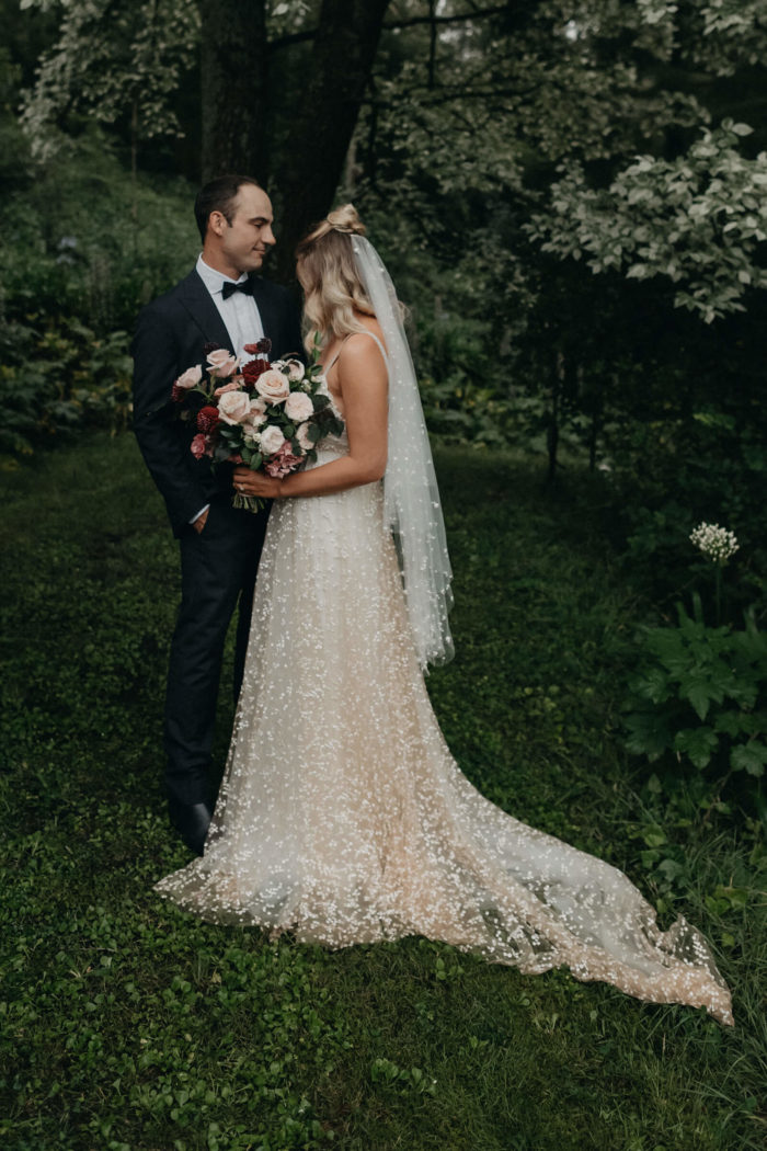 Blonde bride wearing Grace Loves Lace Menha Gown and matching veil holding bouquet standing with groom