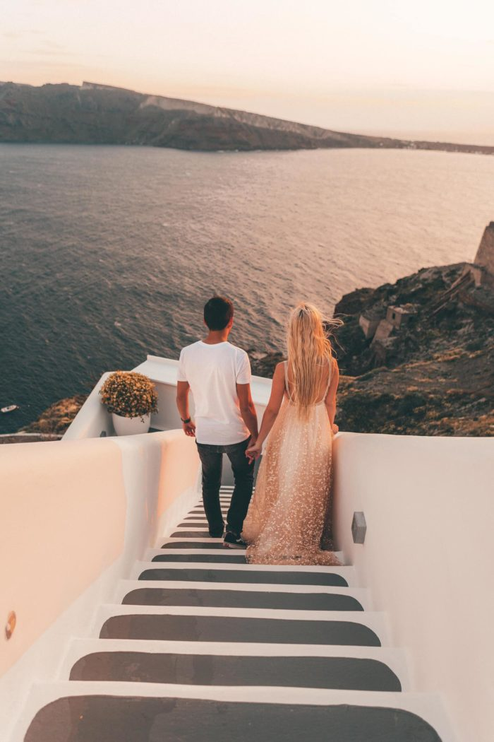 Blonde bride wearing Grace Loves Lace Menha Gown holding hands with groom walking down stairs to ocean