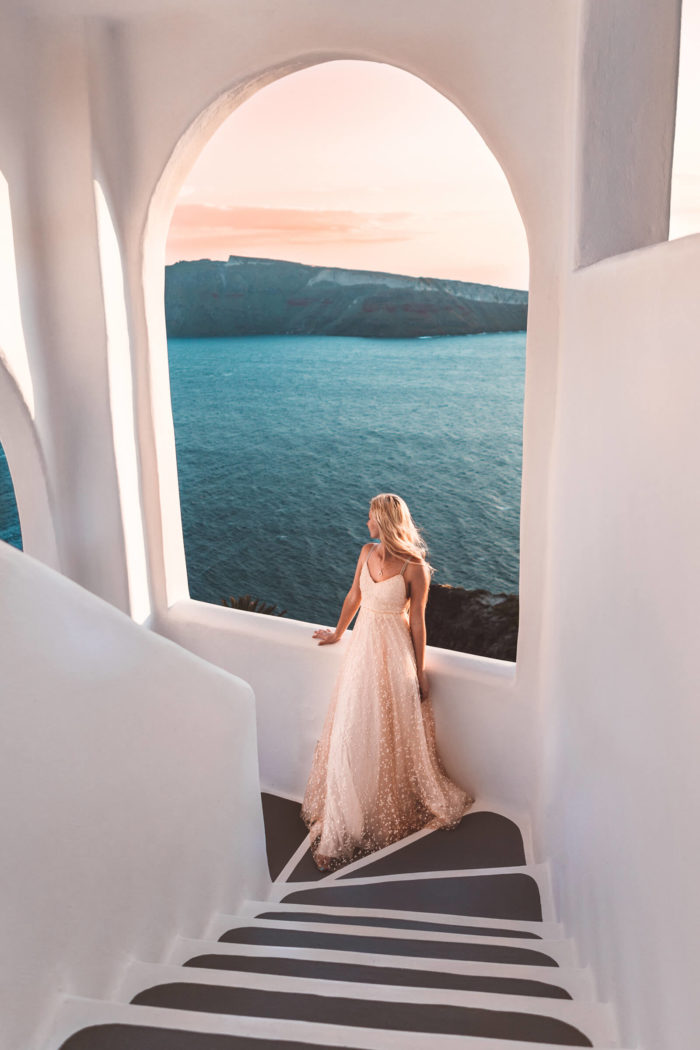 Blonde bride wearing Grace Loves Lace Menha Gown leaning against windowsill on stairs near ocean