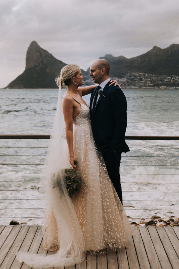 Blonde bride wearing Grace Loves Lace Menha Gown holding bouquet looking at groom near ocean