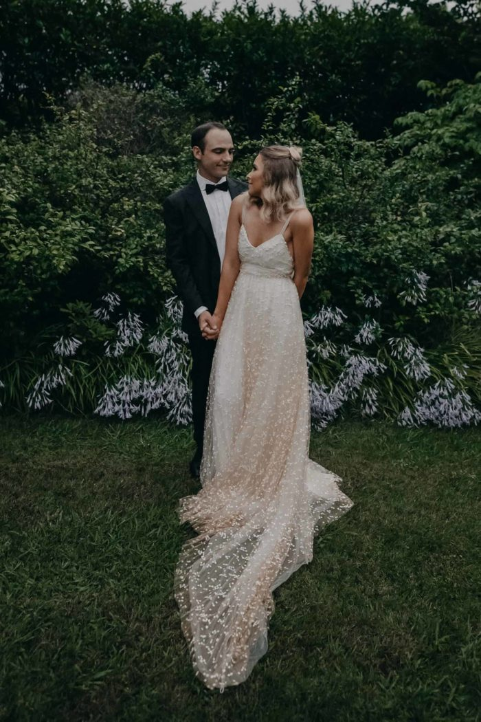 Blonde bride wearing Grace Loves Lace Menha Gown being held by groom